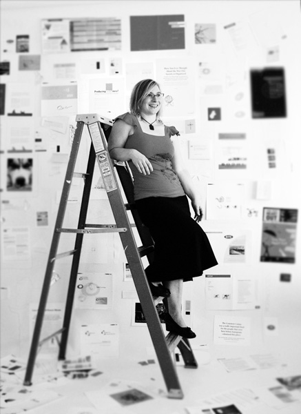 Rebecca standing on a ladder amidst a design portfolio